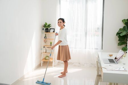 Young Asian woman doing cleaning at the home office.