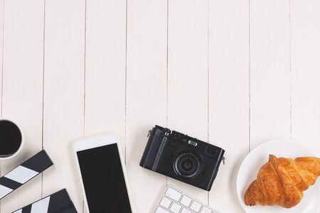 Film sign with smartphone, camera, cake, keyboard on wood background