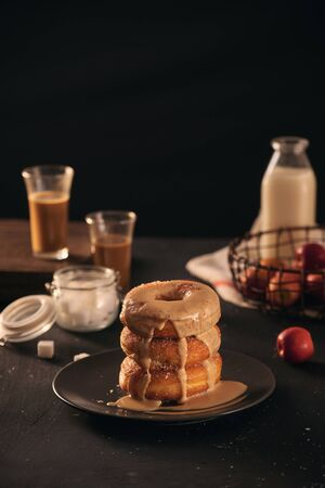 Close-up of donuts in stack with milk bottle and glass