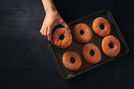 Man hold the donut with sugar coat on the tray