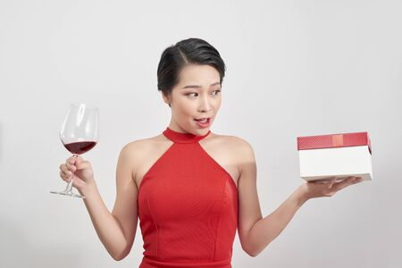 Young smiling woman hold christmas gift box. Isolated portrait of a beautiful girl with wine glass on studio background.