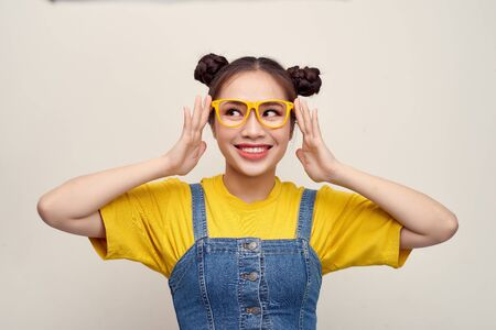 Beautiful Asian woman has two buns of hair wearing a jeans dungaree and adjusting glasses Фото со стока
