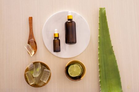 bottle of aloe vera essential oil with peeled aloe - beauty treatment