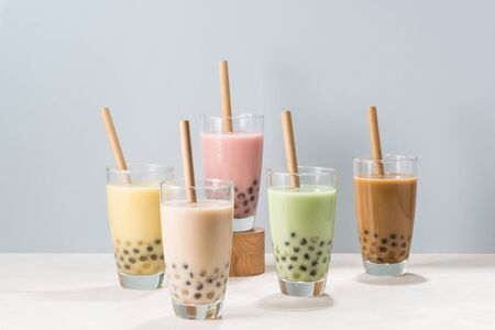 Five glasses of healthy milky boba or bubble tea flavored with fresh fruit and chocolate and served with traditional wide straws Stockfoto