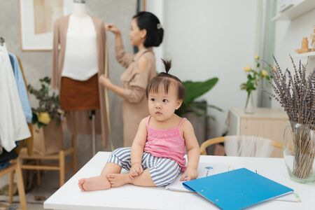 Fashion designer measuring size for tailor made while her baby sitting on table