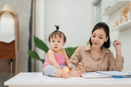 Little baby girl looking at camera while sitting on office desk with her mother in office Stock Photo