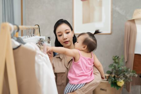 Young beautiful designer  working on her atelier while standing with her baby girl Stock Photo