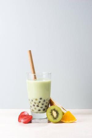 Boba buble tea  glass with kiwi, strawberry, orange slices on blue background. Stock Photo