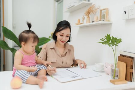 Little baby girl using pen while sitting on office desk with her mother in office