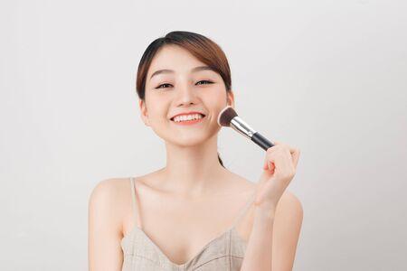 Mujer alegre está haciendo maquillaje en su rostro con pincel. Rutina de belleza sobre fondo blanco.