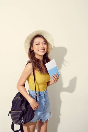 Sunny lifestyle fashion portrait of young woman wearing trendy outfit, straw hat, travel with backpack 写真素材