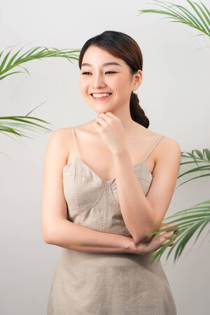 Portrait of Asian happy woman standing with green leaves around her on white background