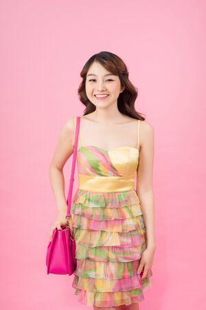 Schönes und süßes Mädchen in einem Blumenkleid mit einer Tasche in der Hand