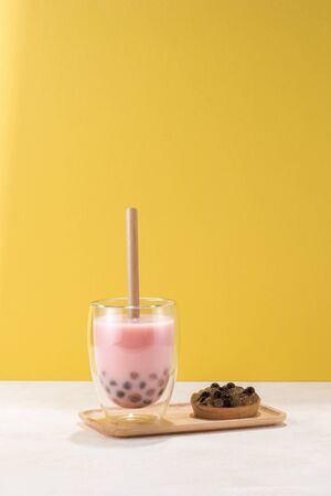 Strawberry flavor boba tea / buble tea with a plate of tapioca ball on yellow background
