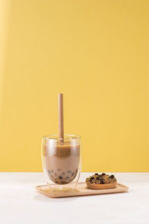 A glass cup of pearl milk tea (also called bubble tea) and a plate of tapioca ball on yellow background.