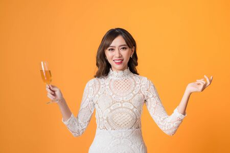 Young beautiful sexy woman in white fashion dress drinking alcohol cocktail