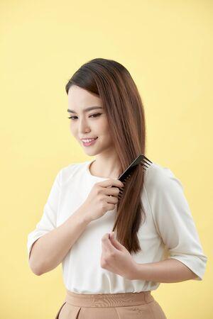 young beautiful woman combing her hair Stockfoto