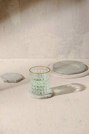 Sun shadow on the table with glass of water, marble plate