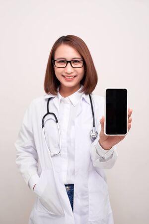 Doctora sonriendo y mostrando una pantalla de teléfono inteligente en blanco aislado en un fondo blanco. Foto de archivo