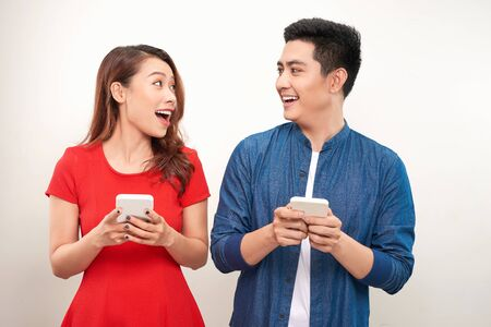 Beautiful smiling modern couple in casual wear with phones in hands on a white wall background