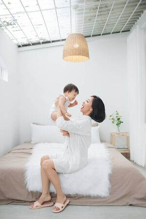Young mother playing with her little girl at the bedroom 免版税图像