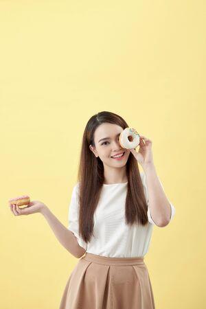 Jolie femme asiatique tenant deux beignets avec une expression souriante mignonne sur fond jaune