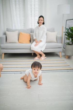 Kleines Mädchen krabbelt auf dem Boden im Wohnzimmer