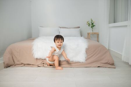 Little girl sitting near the bed at home. Kid at home concept.