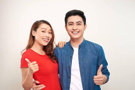 Jeune couple sur fond isolé souriant avec un visage heureux regardant et pointant sur le côté avec le pouce vers le haut