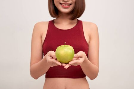 Fitness woman eating apple wearing measuring tape. Fit sporty multicultural Asian  Caucasian female fitness woman isolated on white background. - Image