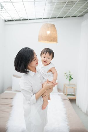 Portrait of happy young mother with baby in bedroom