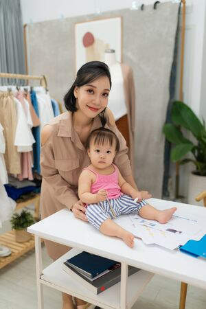 Working together. Young beautiful designer standing near her baby girl at her working place Stock Photo