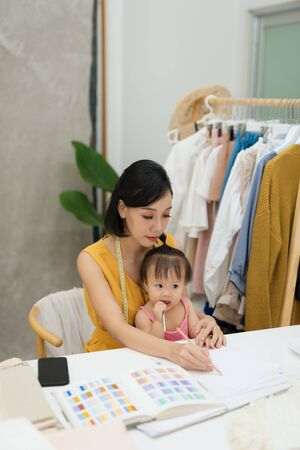 Young woman working with baby on her knees Stock Photo
