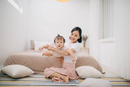 portrait d'une mère asiatique et d'un bébé se relaxant dans la chambre