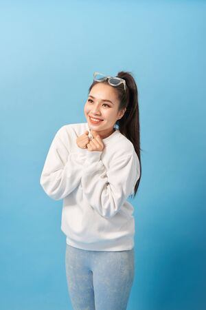 Happy woman keeps hands under chin looks joyfully at camera, notices something very pleasant, isolated over light blue background Stok Fotoğraf