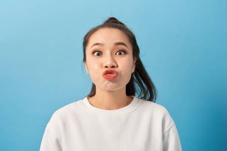 Portrait of adorable woman pouts lips and foolishes alone isolated over blue background