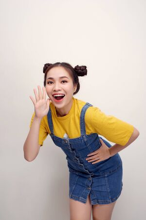 Portrait of pretty joyful woman with two buns holding hands at face and calling aside isolated over white background 스톡 콘텐츠