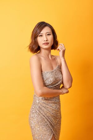 Beautiful female posing in long golden party dress over yellow background