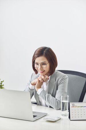 Beautiful business woman smile sitting at the desk working using laptop looking at screen typing on laptop over white background