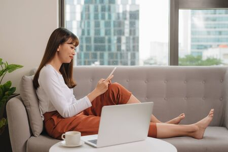 Young woman in casual clothes sitting on sofa at cozy home interior. Technology and communication concept. Imagens