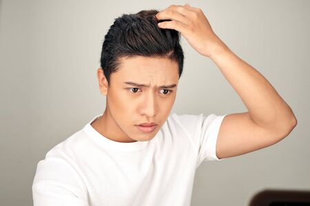 young Asian man worrying about his hair