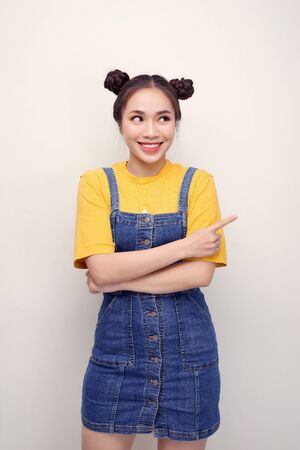 Close up photo beautiful amazing she her lady buns show indicate direct index finger empty space new product wear casual t-shirt jeans denim overalls clothes isolated white background 写真素材