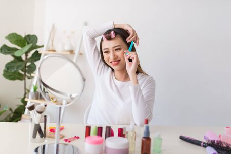 Hairstyle tutorial. Asian woman brushing her hair and smiling pleasantly while filming a tutorial for her beauty blog Stockfoto
