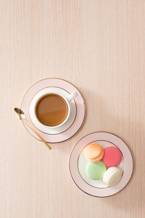 Cup of coffee with macaroons on wooden background