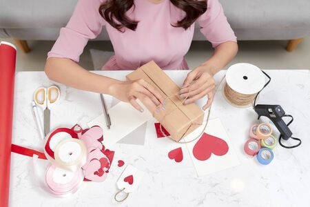 Woman wrapping Christmas gifts. Merry Christmas! Stock fotó