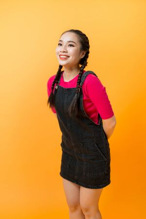 Young cheerful girl having fun. Smiling Woman with bright makeup and hairstyle with pigtails Фото со стока