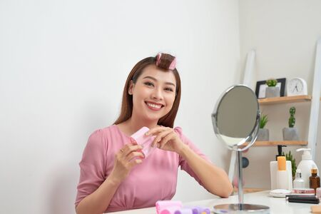 Head and shoulders portrait of beautiful Asian woman wearing hair curlers looking in mirror with wide smile, home interior on background Zdjęcie Seryjne