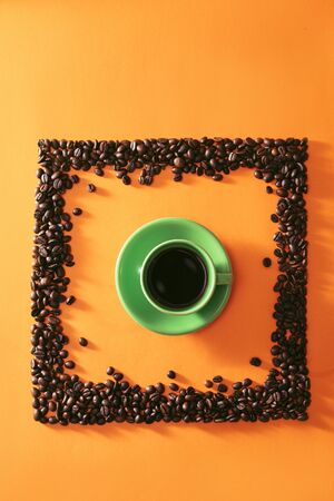 Green cup of coffee in the middle of quare shape coffee beans on orange background