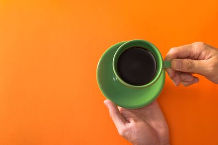 Taking green cup of coffee on orange background flat lay