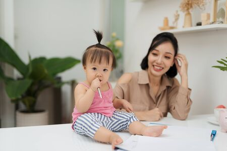 Little assistant. Little baby girl using pen while sitting on office desk with her mother in office Stock Photo